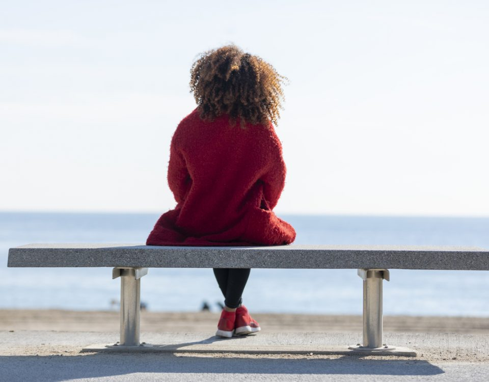Woman looking out to see, thinking about mind-gut connection, in red